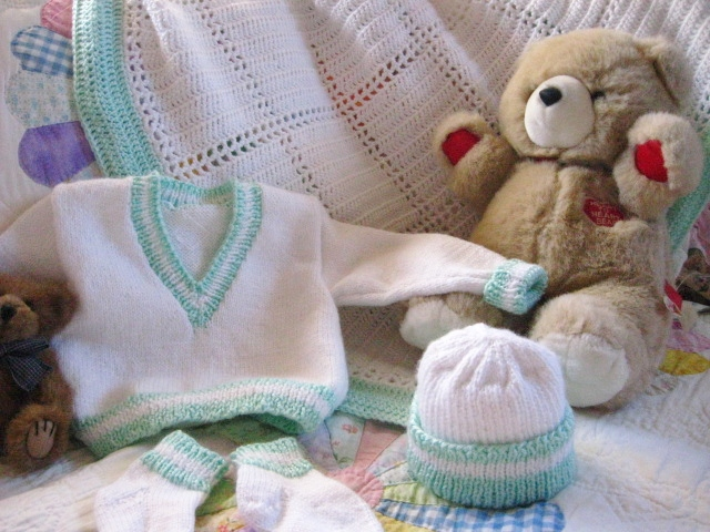 Teddy bear next to green and white layette set.
