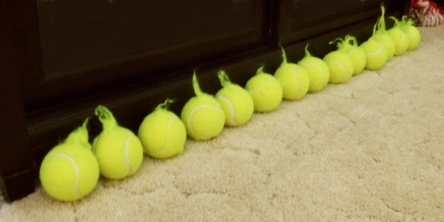 Row of tennis balls from a different angel. All show fuzz handles on them.