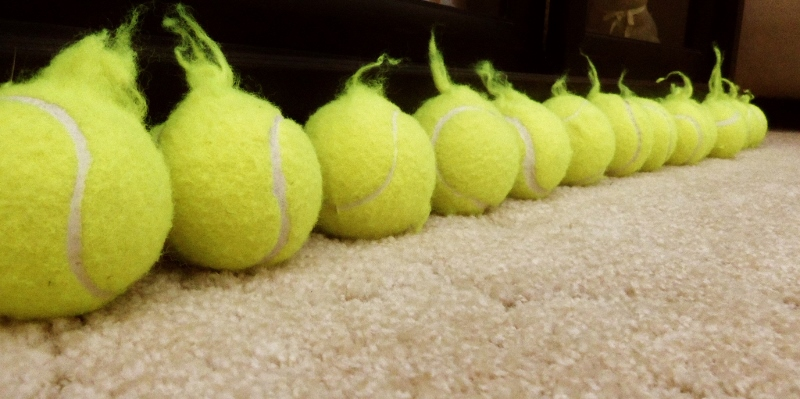 Tennis balls with fuzz handles that a puppy has chewed from their covers.