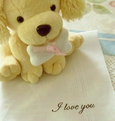 Hand painted handkerchief that says I Love You with stuffed puppy sitting atop it.