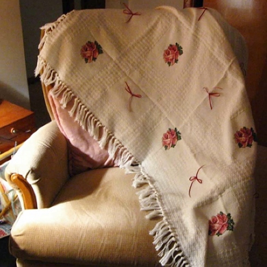 Cross stitched afghan with roses and bows on it.