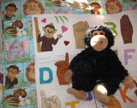 Handmade ASL/American Sign Language Quilt with stuffed monkey posing on top.